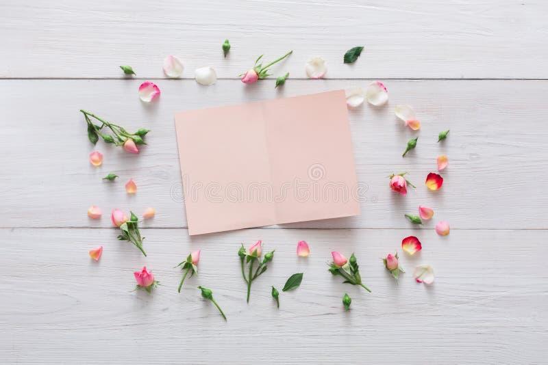 Valentindagbakgrund, pappers- kort och blommor på vitt trä arkivbilder
