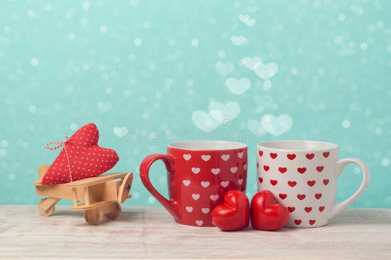 Valentindagbegrepp med par av kaffekoppar och leksakflygplanet arkivfoton