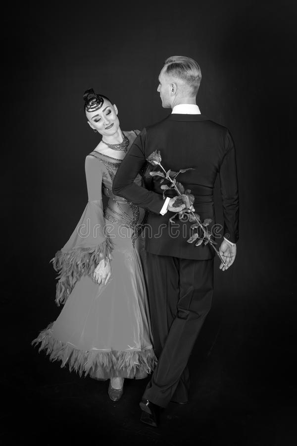 Valentindagberöm Den sinnliga kvinna- och mandansen med rosen blommar Kvinna i klänning och macho i smoking Par av balsal D arkivfoton