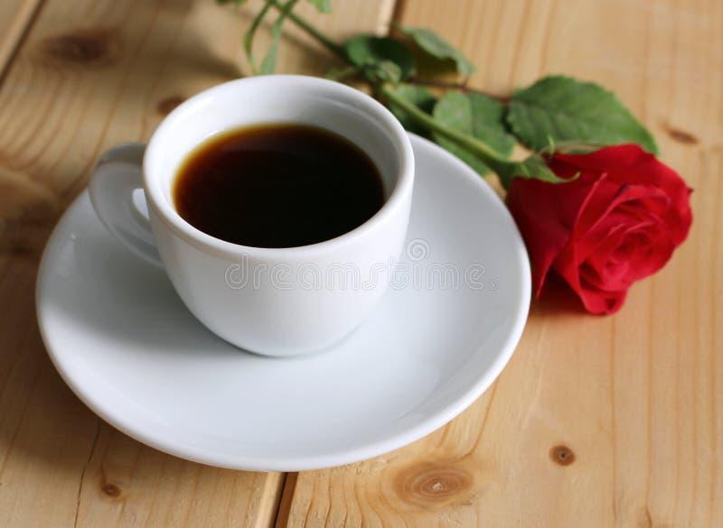 Valentindagen, platsen med koppen kaffe och röda blommor steg på trätabellen man för begreppskyssförälskelse till kvinnan suddigh royaltyfria foton