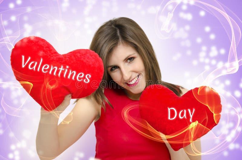 Valentindagflicka som rymmer två hjärtor arkivfoton