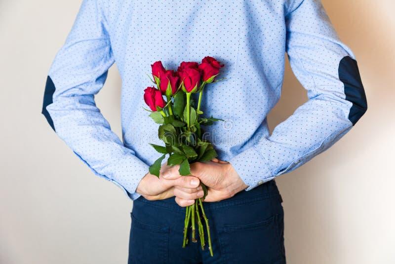 Valentindaggåva, stilig för nederlagöverraskning för ung man som gåva behing hans baksida royaltyfria foton