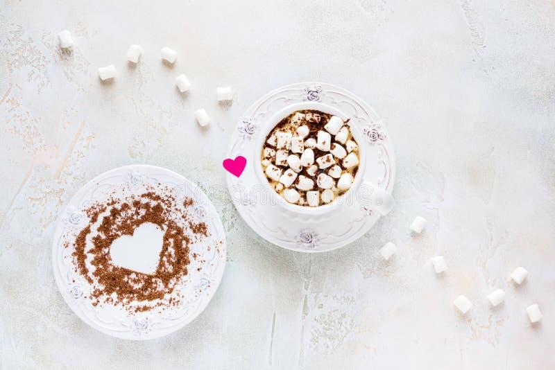 Valentindaggarnering, frukost, vit tappningkopp och platta, kaffe med små marshmallower och hjärtor som göras från rött papper royaltyfri foto