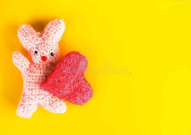 Valentindagkort med den virkade handgjorda leksakkaninen och dekorativ hjärta royaltyfri foto