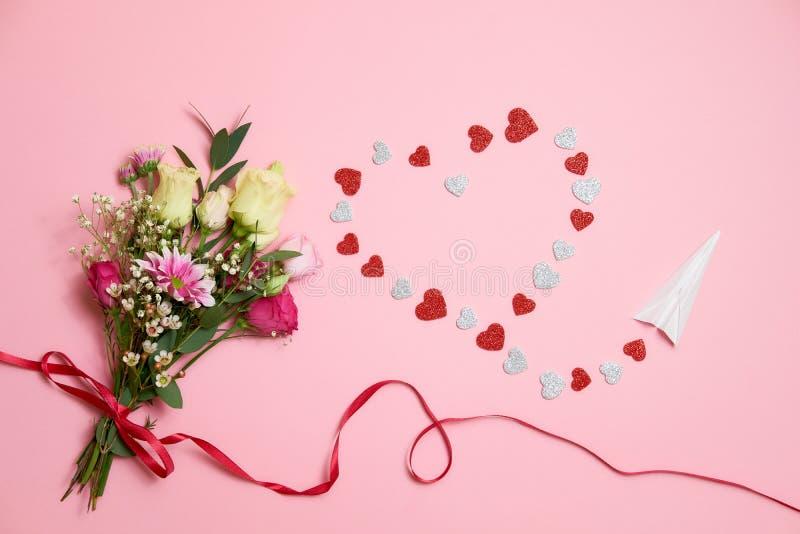 Valentindagsammansättning: buketten av blommor med bandpilbågen, hjärtahjärtaform gjorde av valentinkort och pappersflygplanet Lo royaltyfri bild