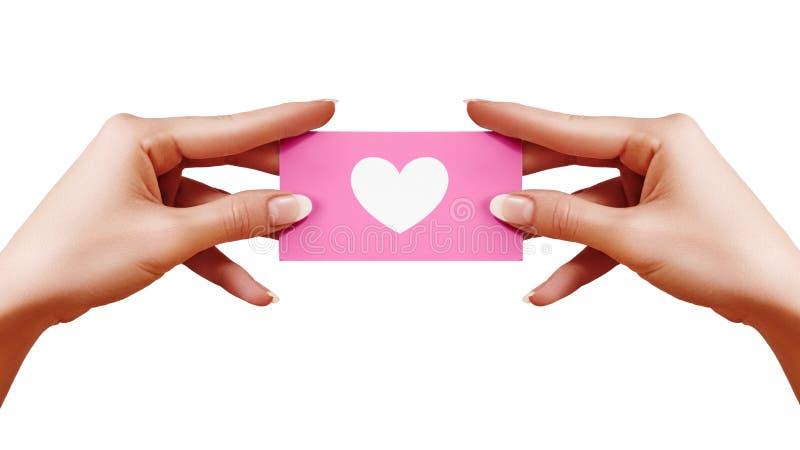 Valentindagvykort med formhjärta i kvinnlig hand på vit bakgrund Rosa gåvakort Förälskelse- och lyckasymbol arkivbild