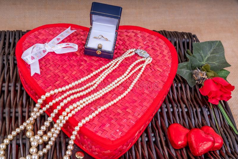 Valentine's Day Gift Hamper. Diamond Ring and Pearl Necklace and gift box with a wicker hamper with Heart shaped chocolates stock image