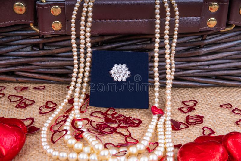 Valentine's Day Gift Hamper. Diamond Ring and Pearl Necklace in front of a wicker hamper with Heart shaped chocolates stock images