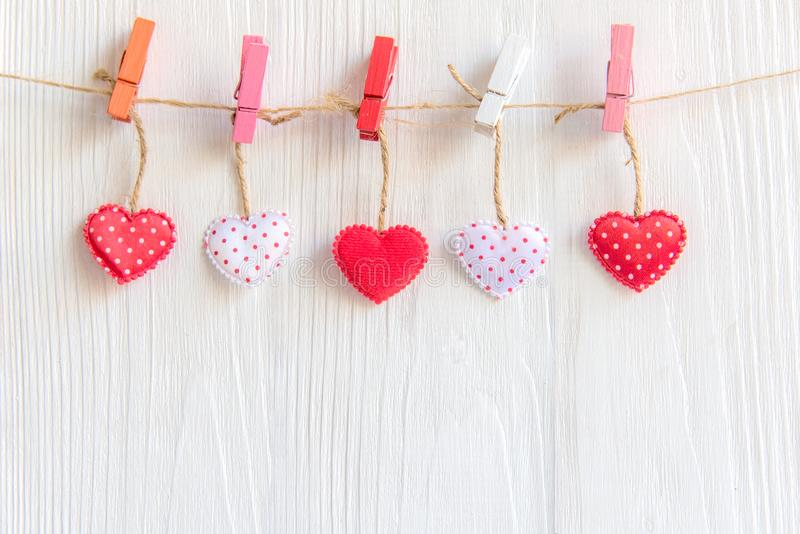 Valentine's Day. Sewed pillow hearts row border on red, pink and white clothespins at rustic white wood planks royalty free stock image