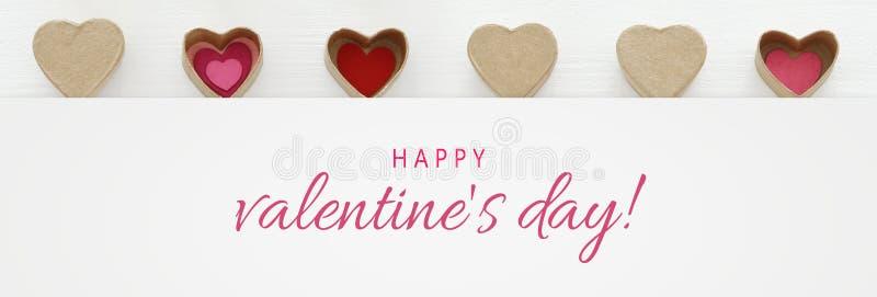 Valentine' έννοια ημέρας του s καρδιές ως κιβώτια δώρων εγγράφου πέρα από το ξύλινο άσπρο υπόβαθρο στοκ φωτογραφία