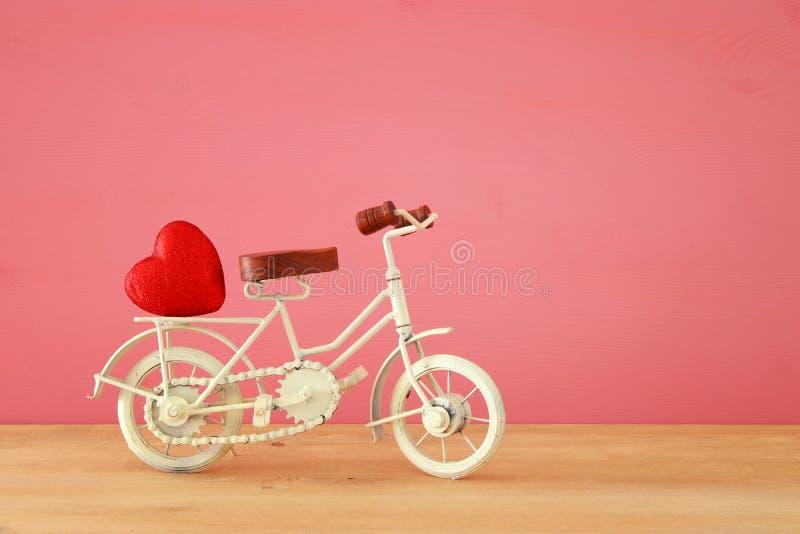 Valentine& x27; 与白色葡萄酒自行车玩具的s天浪漫对此的背景和心脏在木桌 免版税图库摄影