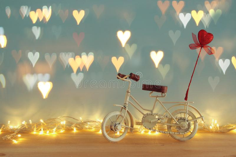 Valentine& x27; 与白色葡萄酒自行车玩具的s天浪漫背景和对此的闪烁红色心脏在木桌 图库摄影