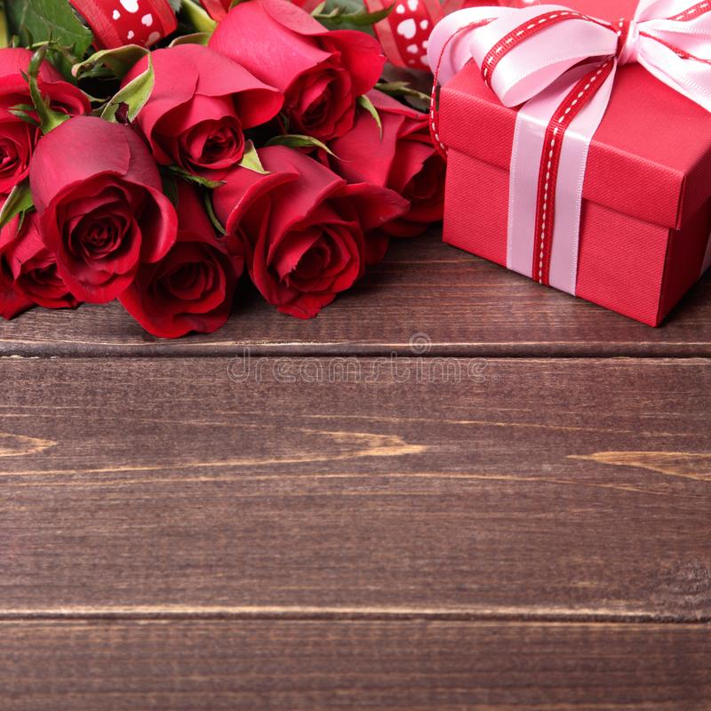 Valentine background of gift box and red roses on wood. Space for copy. Valentine background of gift box and red roses on wood stock photography