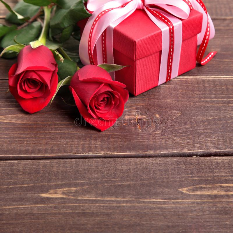 Valentine background of gift box and red roses on wood. Space for copy. Valentine background of gift box and red roses on wood stock image