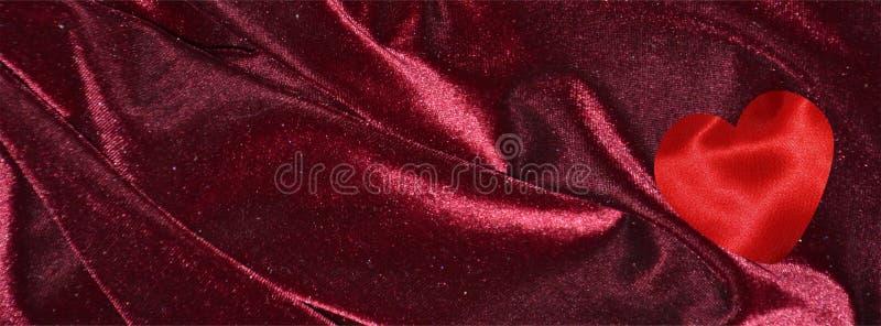 Valentine banner with red silk hearts on Dark burgundy red velvet stock photos