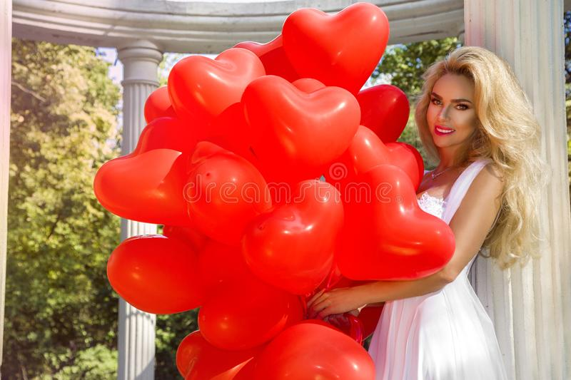 Valentine Beautiful girl with red balloons laugh, in the park. Beautiful happy young woman. stock photo