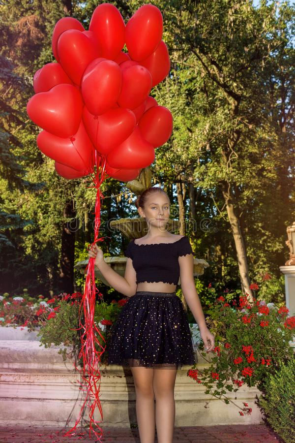 Valentine Beautiful young girl with red balloons laugh, in the park. Beautiful happy kid. Christmas party. Joyful little model. Valentine Beautiful young girl royalty free stock photos