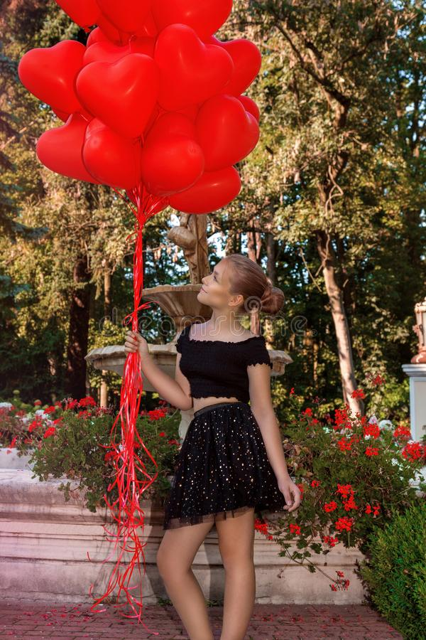 Valentine Beautiful young girl with red balloons laugh, in the park. Beautiful happy kid. Christmas party. Joyful little model royalty free stock photo
