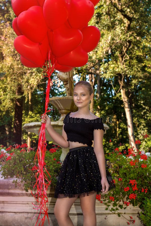 Valentine Beautiful young girl with red balloons laugh, in the park. Beautiful happy kid. Christmas party. Joyful little model royalty free stock photos