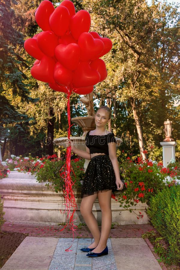 Valentine Beautiful young girl with red balloons laugh, in the park. Beautiful happy kid. Christmas party. Joyful little model. Valentine Beautiful young girl royalty free stock photography