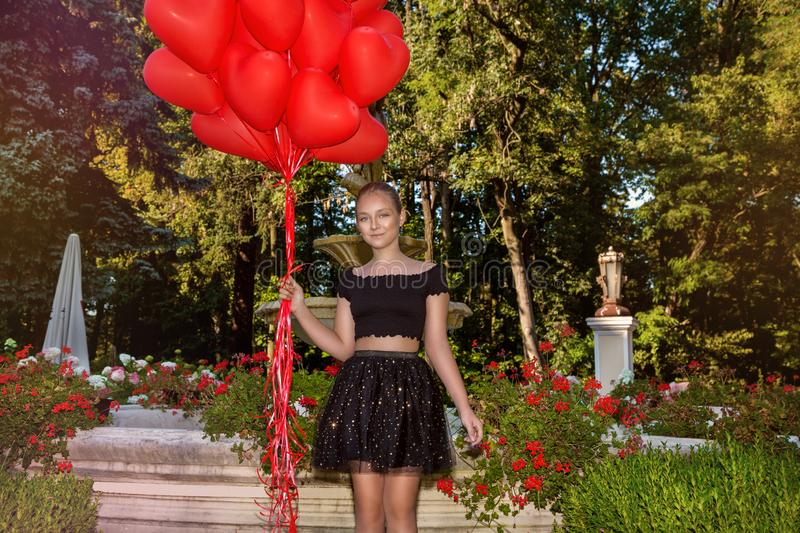 Valentine Beautiful young girl with red balloons laugh, in the park. Beautiful happy kid. Christmas party. Joyful little model. Valentine Beautiful young girl royalty free stock photo
