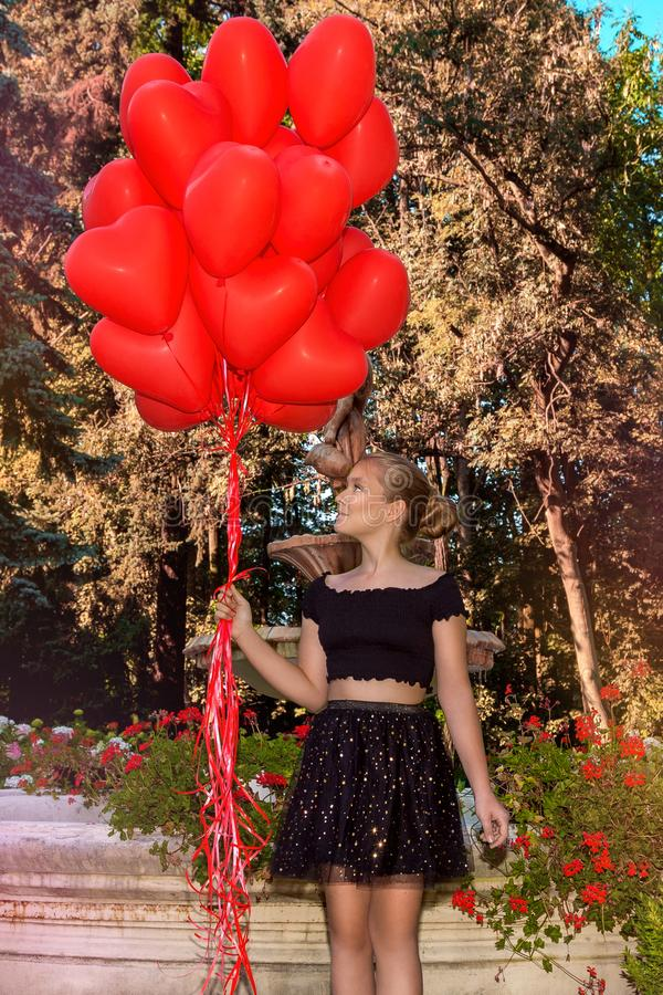 Valentine Beautiful young girl with red balloons laugh, in the park. Beautiful happy kid. Christmas party. Joyful little model. Valentine Beautiful young girl royalty free stock images