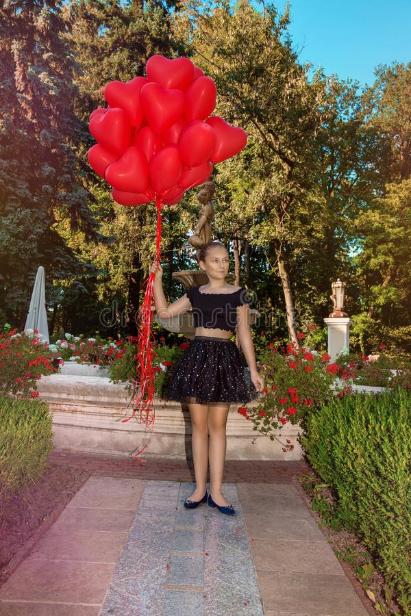 Valentine Beautiful young girl with red balloons laugh, in the park. Beautiful happy kid. Christmas party. Joyful little model royalty free stock photography