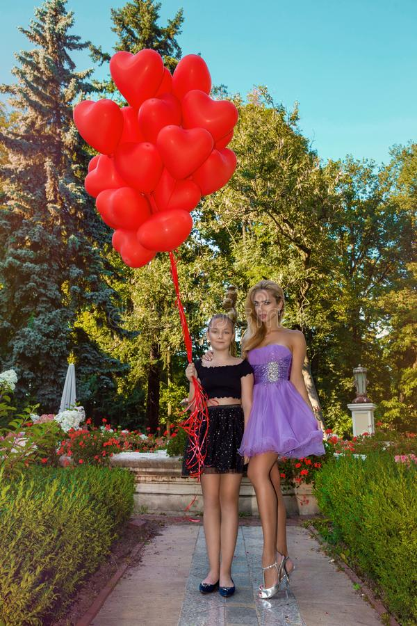 Valentine Beautiful young mother and daughter with red balloons laugh, in the park. Beautiful happy mom and kid. Birthday party. royalty free stock photography