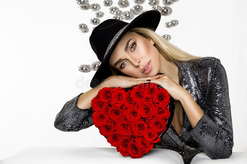 Valentine Beauty girl with red heart roses. Portrait of a young female model with gift and hat, isolated on background. royalty free stock photos