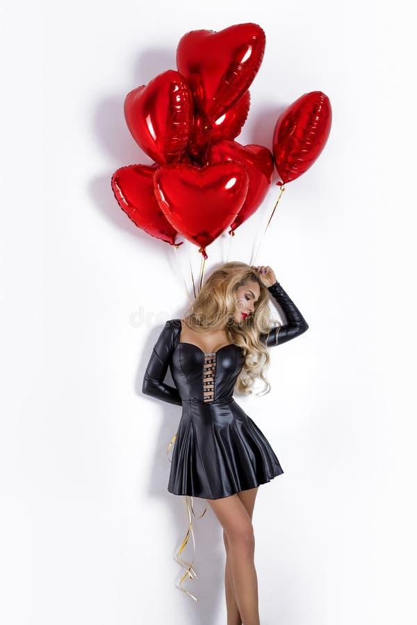 Valentine Beauty-Mädchen mit dem roten Luftballon lokalisiert auf weißem Hintergrund Schöne glückliche junge Frau, die Produkt da stockbild