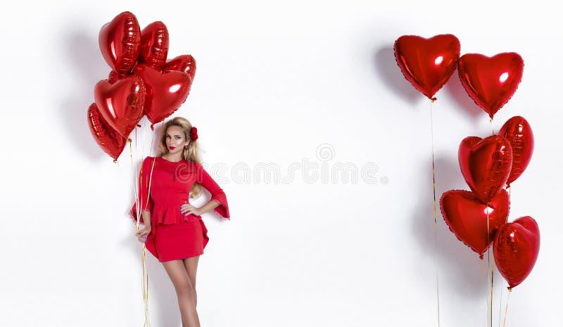 Valentine Beauty-Mädchen mit dem roten Luftballon lokalisiert auf weißem Hintergrund Schöne glückliche junge Frau, die Produkte d lizenzfreies stockbild