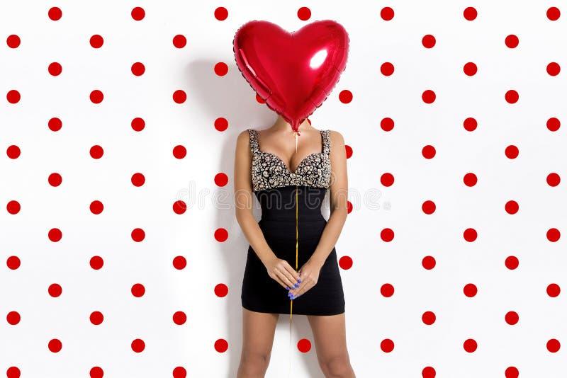 Valentine Beauty-Mädchen mit dem roten Luftballonporträt, lokalisiert auf Tupfenhintergrund Modell bedeckt ihr Gesicht mit einem  lizenzfreie stockfotografie