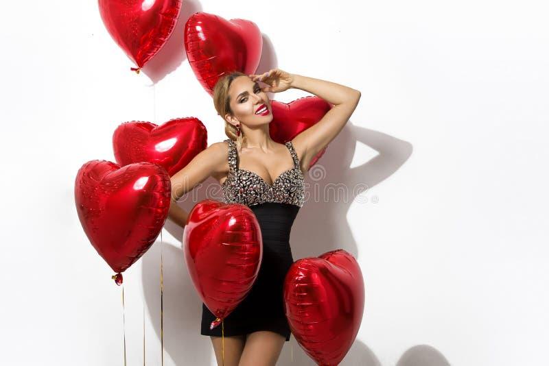 Valentine Beauty-Mädchen mit rotem Luftballonporträt die Hand zeigend, lokalisiert auf Hintergrund lizenzfreie stockfotografie
