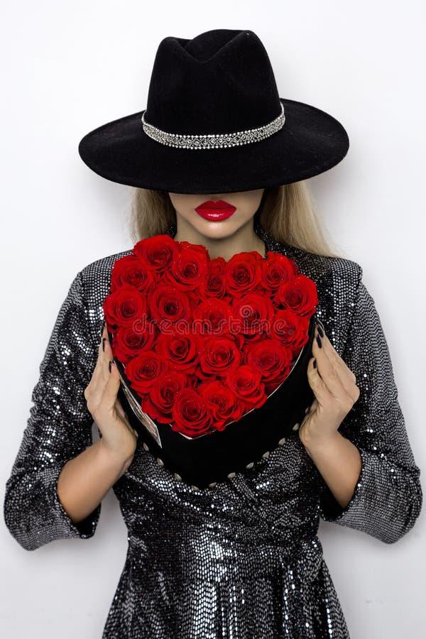Valentine Beauty-meisje met rode hartrozen Portret van een jong vrouwelijk die model met gift en hoed, op achtergrond wordt geïso royalty-vrije stock afbeeldingen