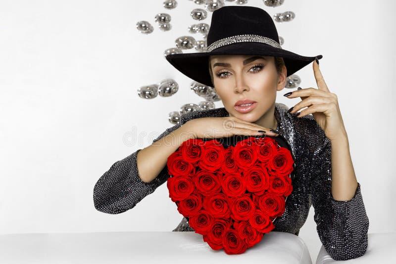 Valentine Beauty-meisje met rode hartrozen Portret van een jong vrouwelijk die model met gift en hoed, op achtergrond wordt geïso royalty-vrije stock afbeelding