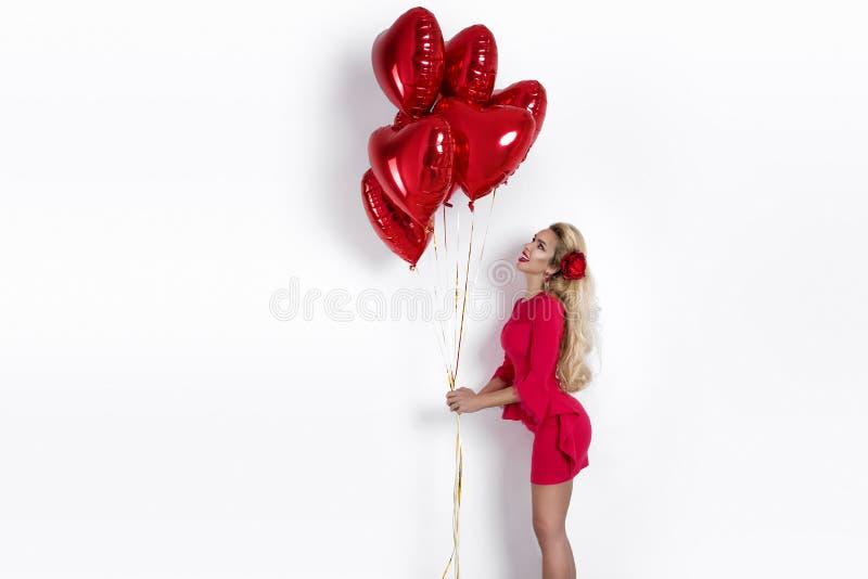 Valentine Beauty-meisje met rode luchtballon op witte achtergrond Mooie Gelukkige Jonge vrouw die producten voorstellen stock afbeeldingen