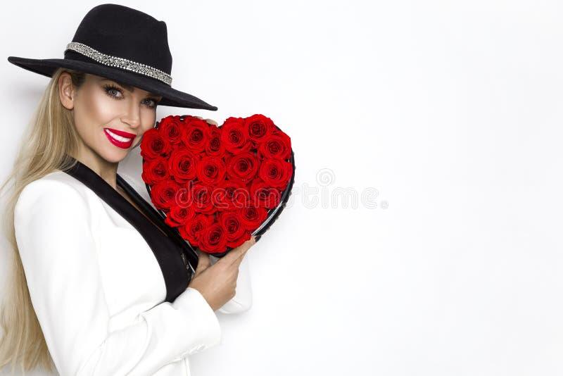 Valentine Beauty, menina elegante com coração vermelho com rosas Retrato de um modelo fêmea novo com presente e chapéu foto de stock royalty free