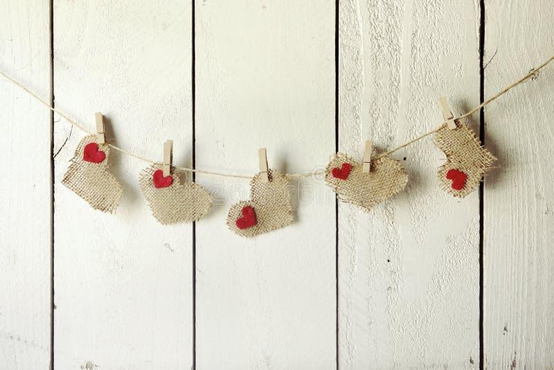 Valentine Burlap Hearts Hanging feliz en una pared de madera imagen de archivo