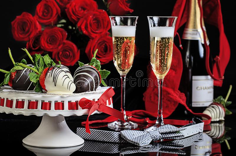 Valentine Champagne Flutes Roses Lingerie. A Valentine Day setting with white and dark chocolated covered strawberries, filled champagne flutes, red roses and royalty free stock photography