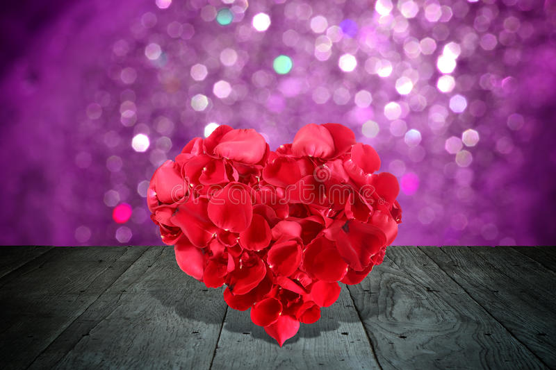 Valentine composition with heart shape made out of rose petals. On wooden deck table with bokeh stock photography