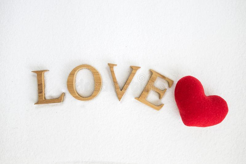 Love text with red heart on white sand royalty free stock photography