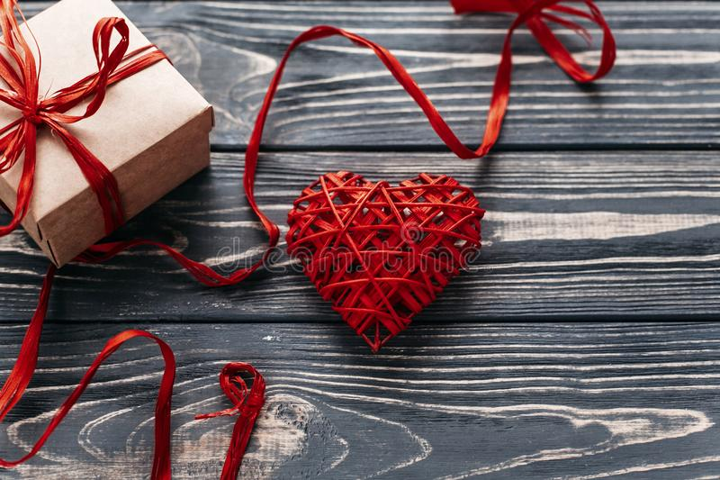valentine concept. stylish red present and heart ribbons on black rustic wooden background. happy valentines day. greeting card w royalty free stock image