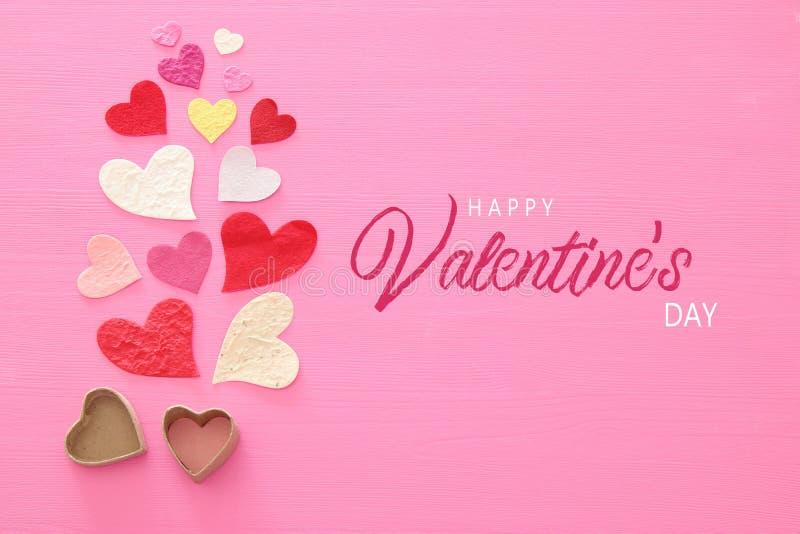Valentine' concepto del día de s Corazones de papel sobre fondo rosado de madera Endecha plana libre illustration