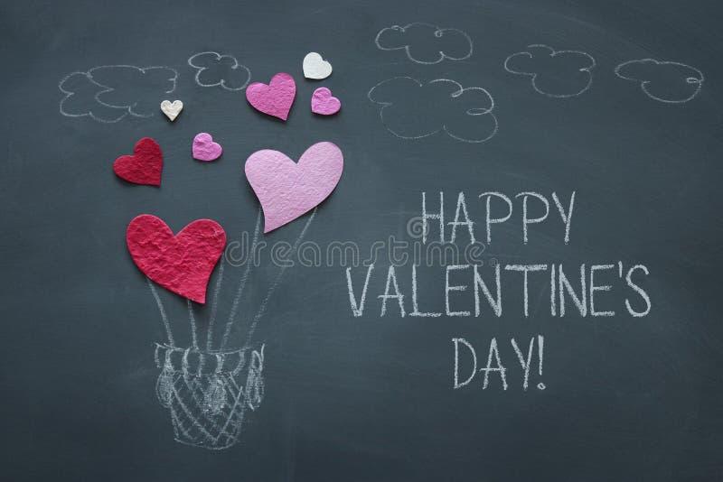 Valentine' concetto di giorno di s rosa e cuori di carta rossi come aerostato sopra la lavagna immagini stock libere da diritti