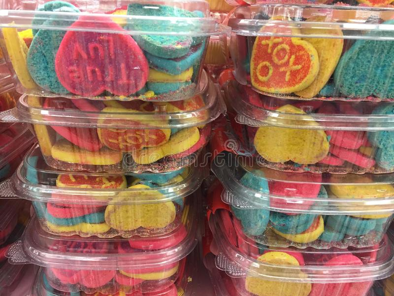 Valentine Cookies for Sale. Commercially made Valentine Cookies for sale at Market. Cookies are packaged in plastic containers. Pink, yellow, blue and red colors royalty free stock image