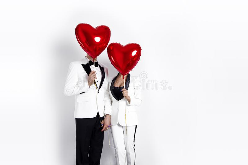 Happy beautiful couple posing on white background and holding balloons heart. Valentine`s day. stock photography