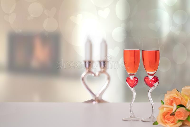 Valentine Day background. A bright table top with two glasses in shape of red hearts with champagner and a bouquet flowers in. Front of abstract blurred stock images