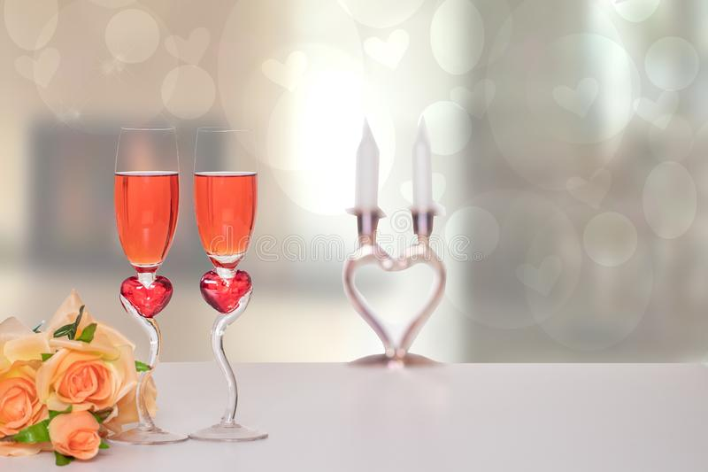Valentine Day background. A bright table top with two glasses in shape of red hearts with champagner and a bouquet in front of. Abstract blurred background stock image