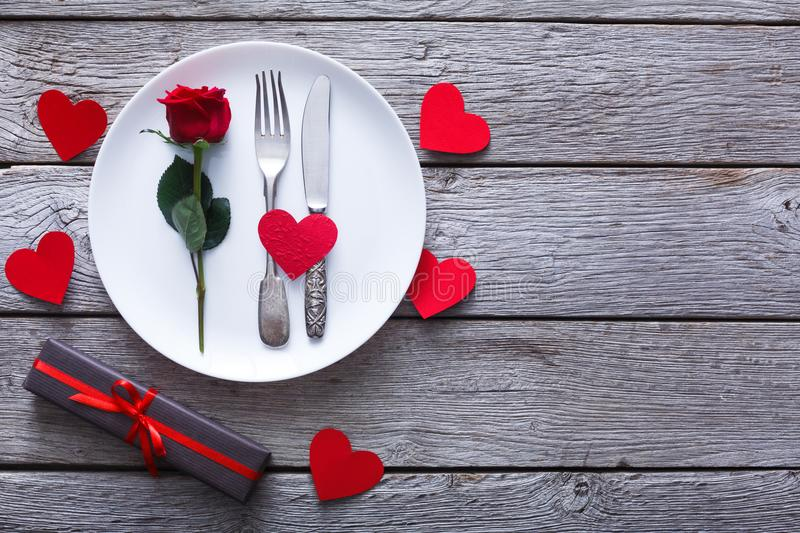 Valentine day background, cutlery with rose on plate on wood stock image