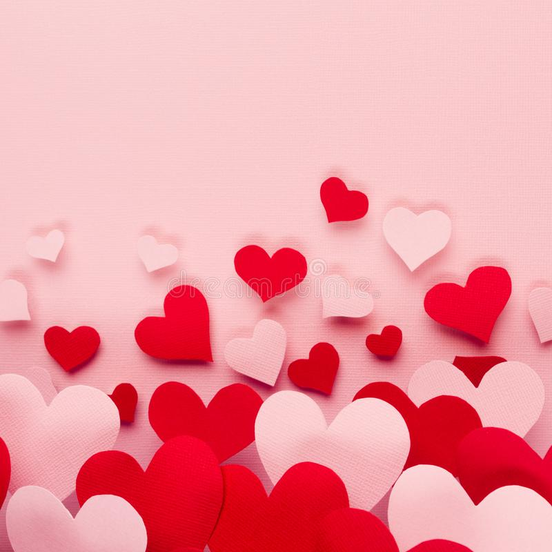 Valentine day background of fly paper red and pink hearts on pink color backdrop. Copy space. royalty free stock images